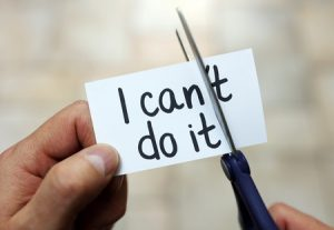 54427907 - man using scissors to remove the word can't to read i can do it concept for self belief, positive attitude and  motivation